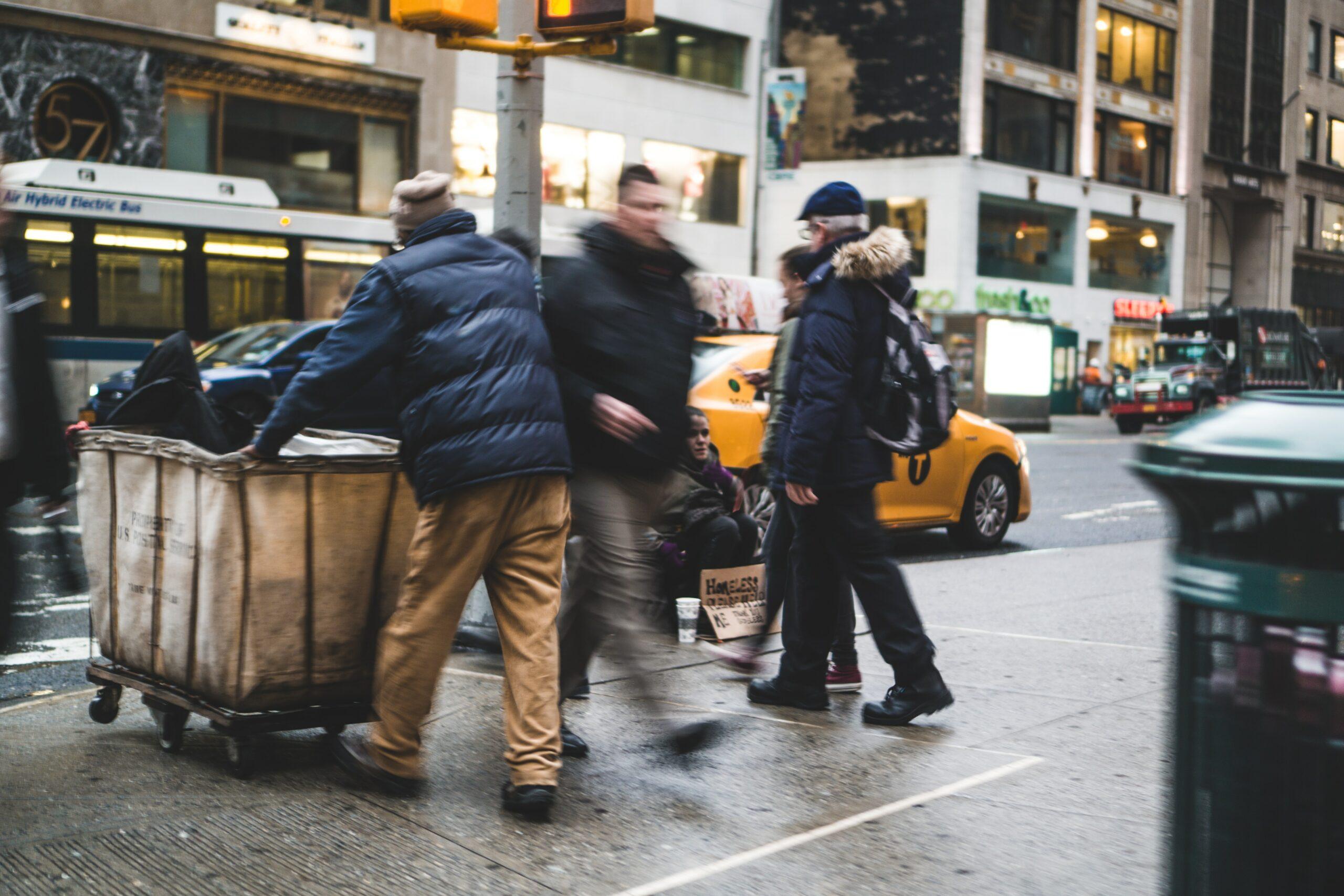 man walking on street beside man pushing cart