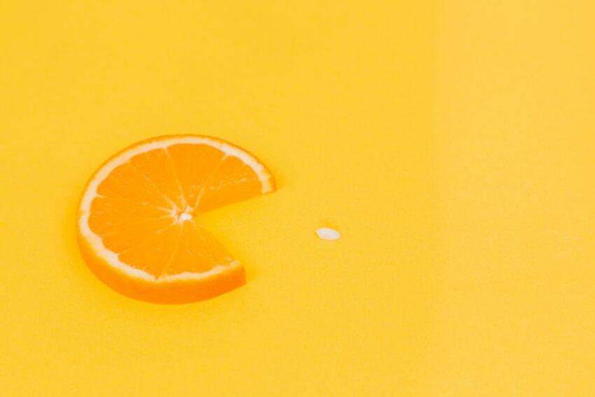 sliced orange fruit on yellow surface